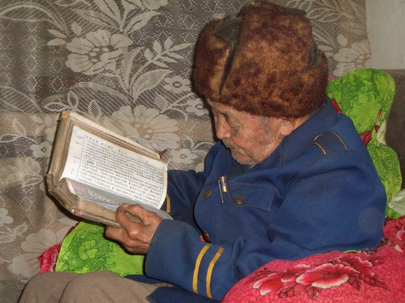 90-year old Chinese man reading Bible-min