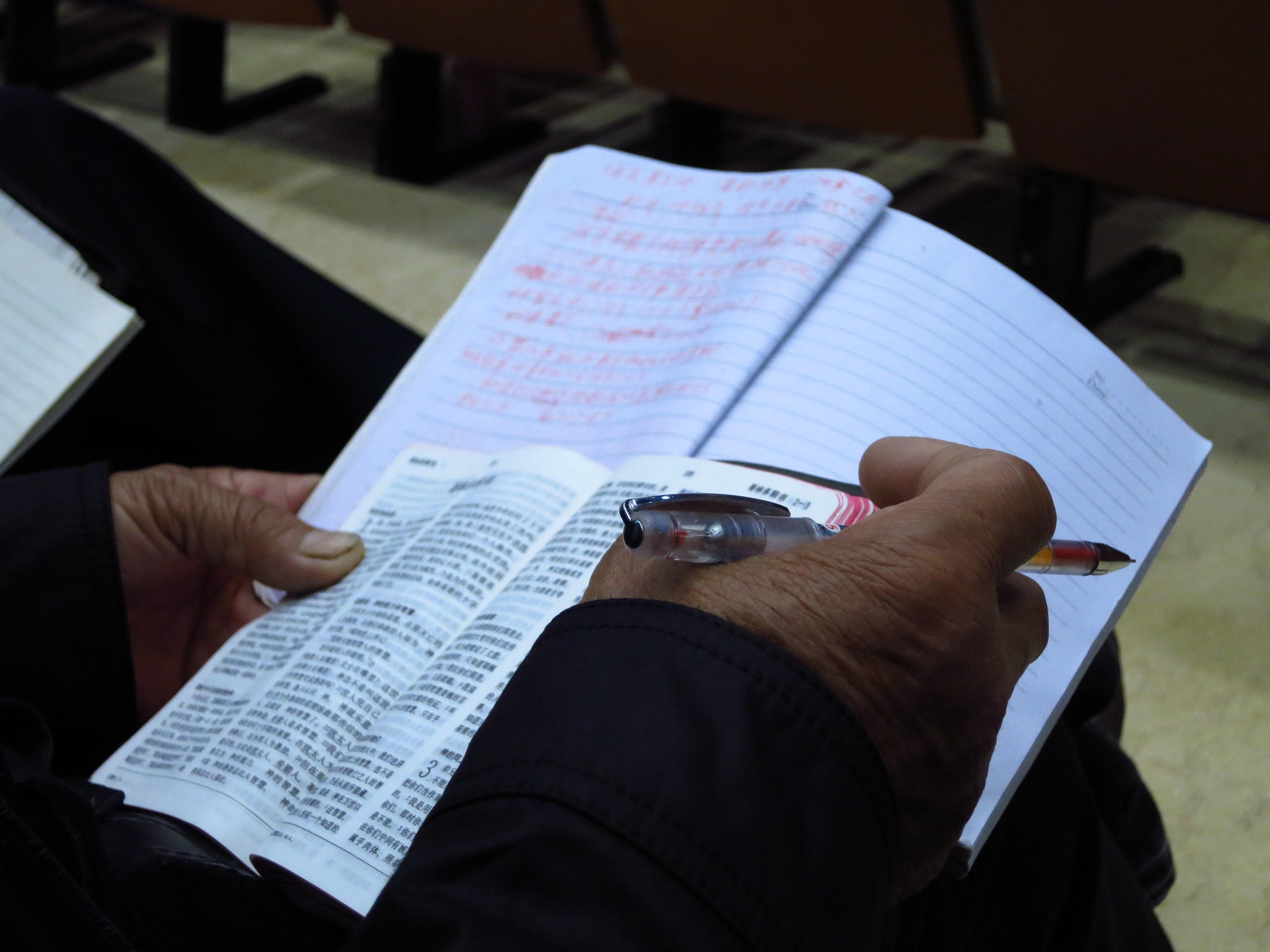 Elderly believer's hands - studying-min