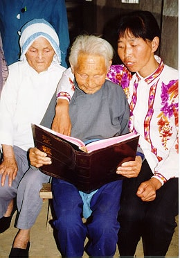 Elderly-woman-flanked-by-two-woman-reading-Bible-min