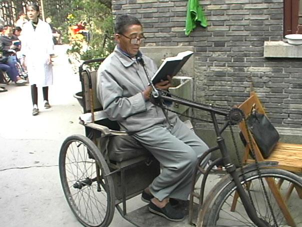 Man-reading-Bible-on-bicycle-min