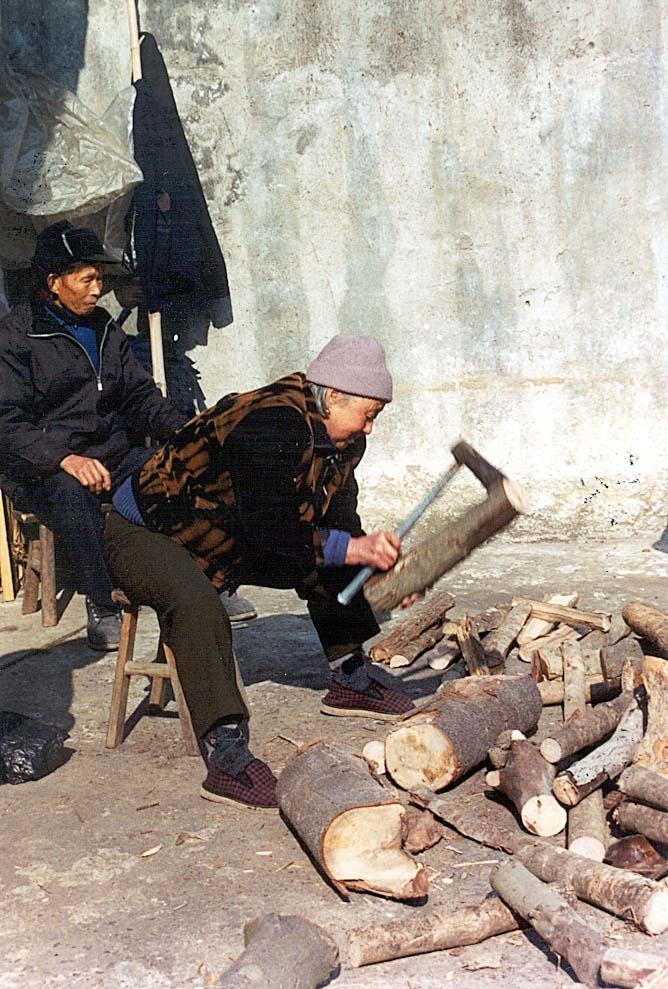 Yaolin church - elderly woman chopping wood-min
